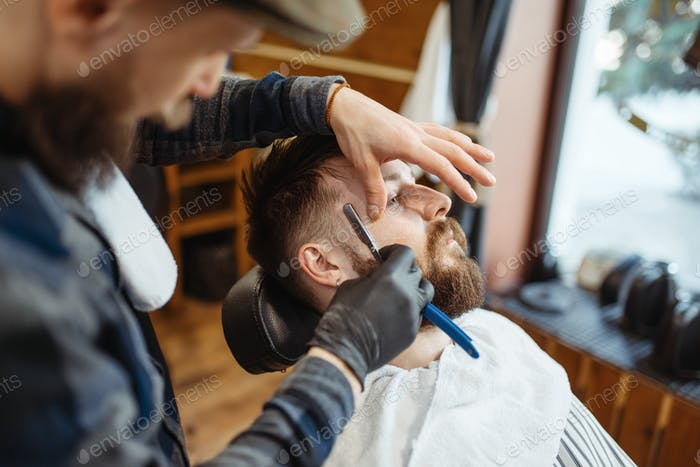 Barber with razor, old school beard cutting