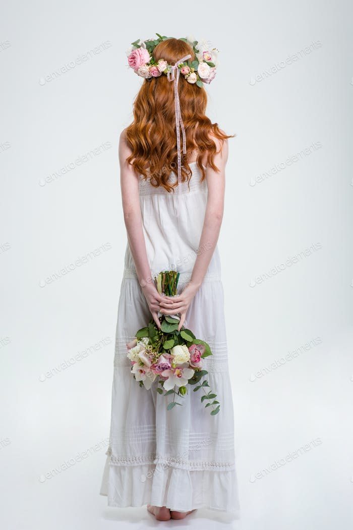 Back view of woman in wreath standing and hiding bouquet