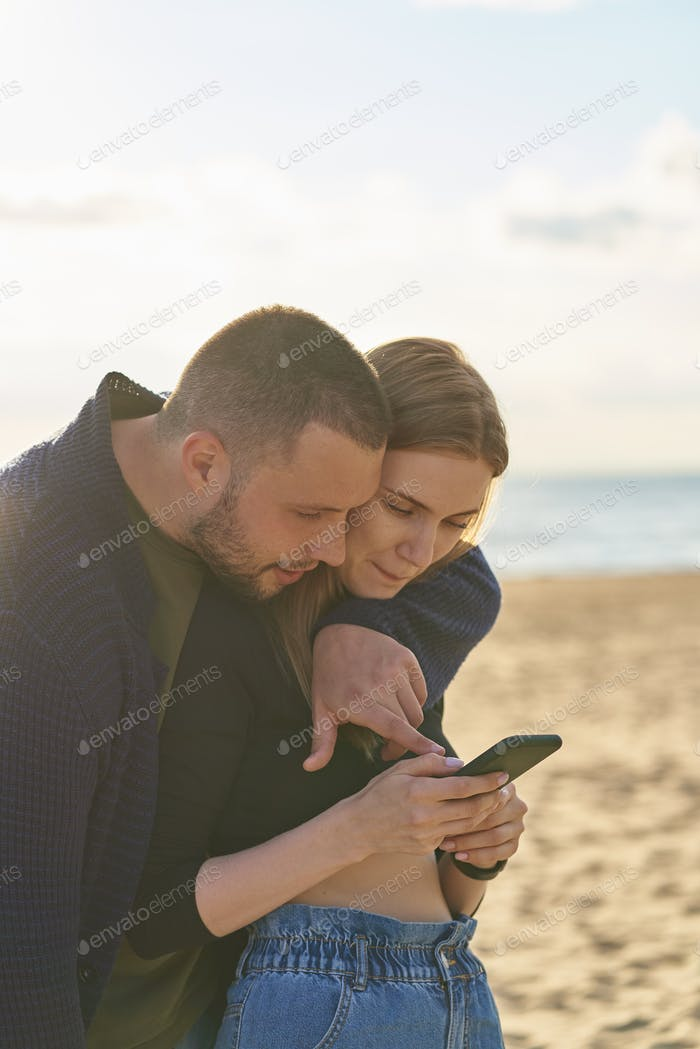 Young couple standing on sandy beach and looking at smartphone, man points finger at mobile