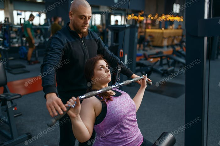 Instructor helps to overweight woman, gym