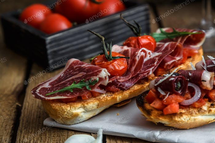closeup shot of an bruschetta with tomatoes salsa, parma, arugula and olives, close view