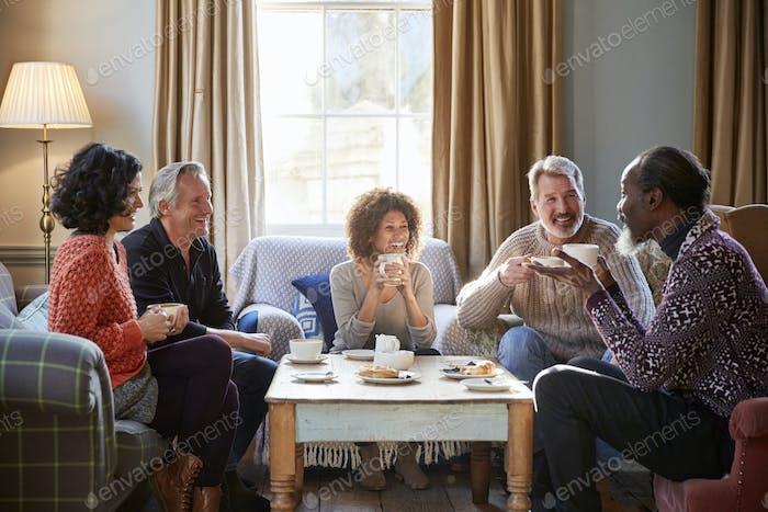 Grupo de Amigos de mediana edad reunión alrededor de la mesa en la cafetería