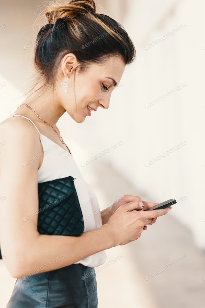 Side view portrait of a smiling elegant young woman using a smart phone