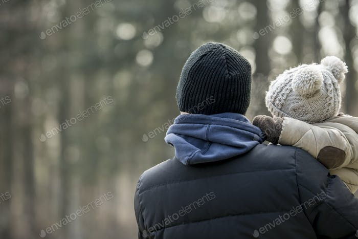 Parent holding a young child on a winter day