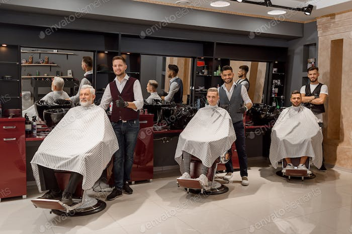 Male clients sitting in hairdresser chairs covered with haircut