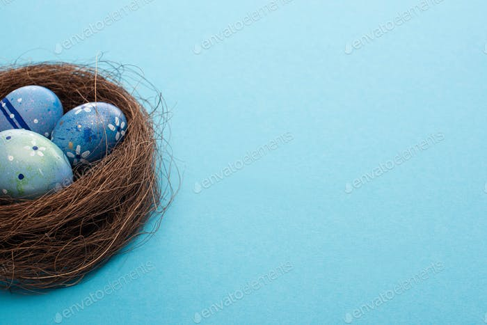 Nest With Painted Chicken Eggs on Blue Background