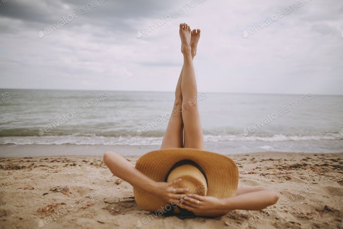 Girl in hat lying on beach with legs up