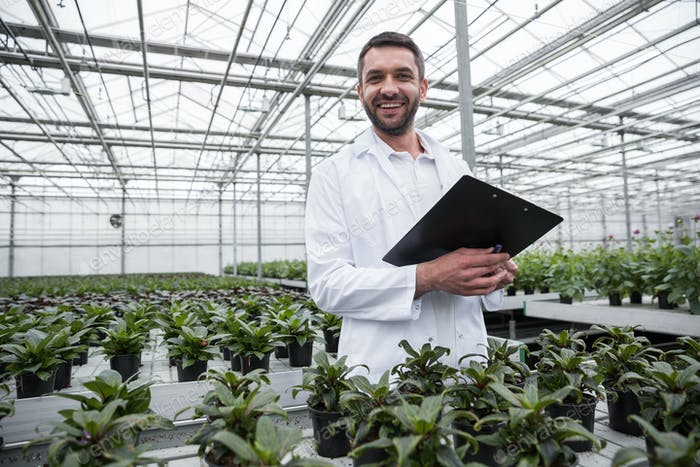 Happy man standing in greenhouse near plants holding clipboard