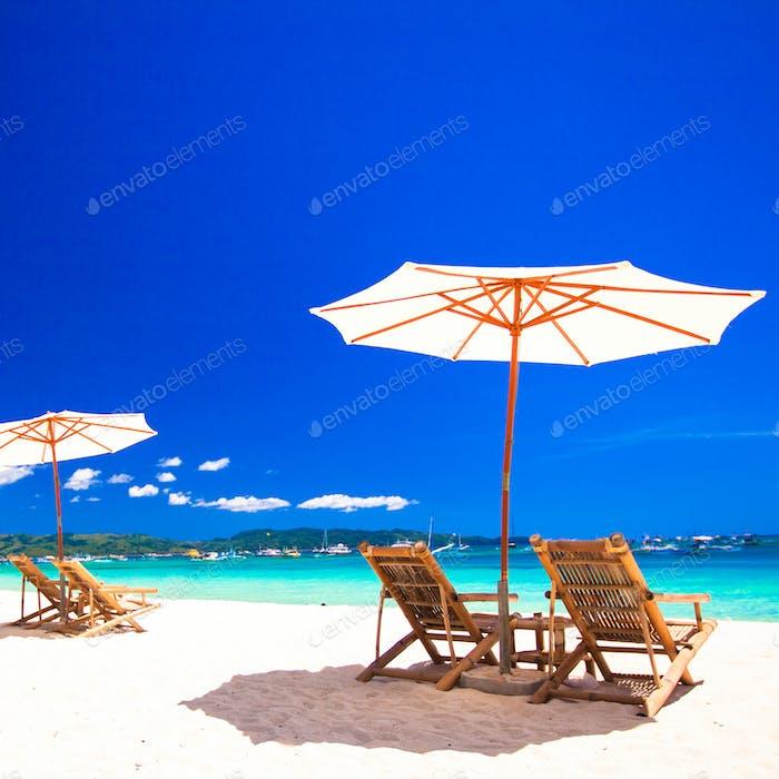 Sillas y sombrillas de madera en la playa de arena blanca frente a la laguna
