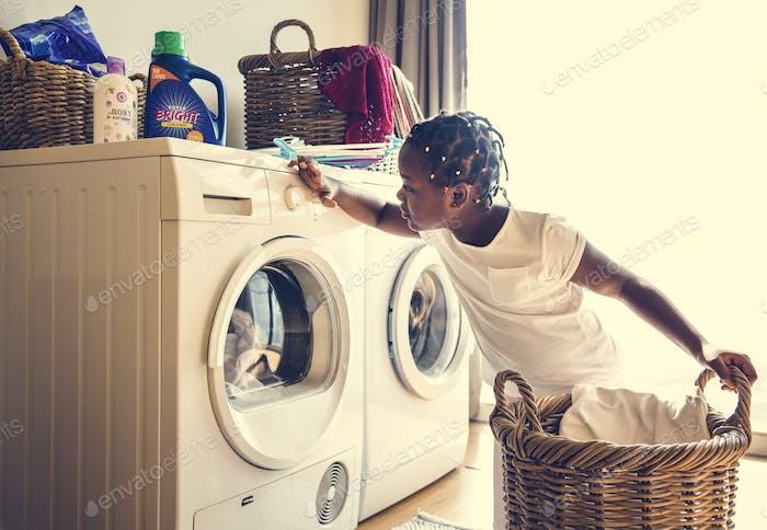 Junge teen Mädchen Waschen Kleidung mit Waschmaschine