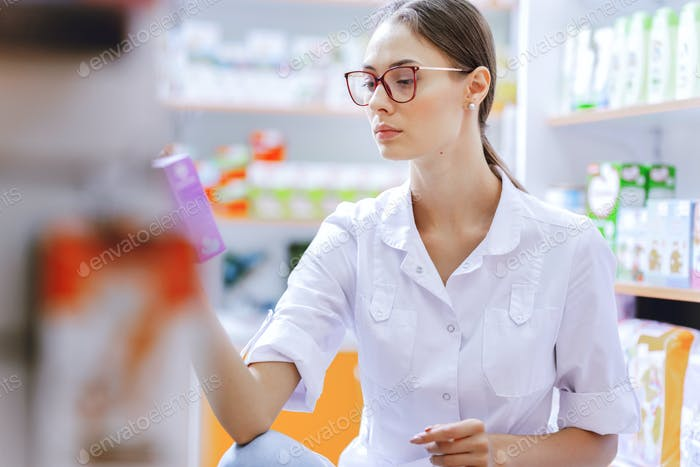 A young thin brown-haired girl with glasses,dressed in a lab coat, crouching,examines medicines on