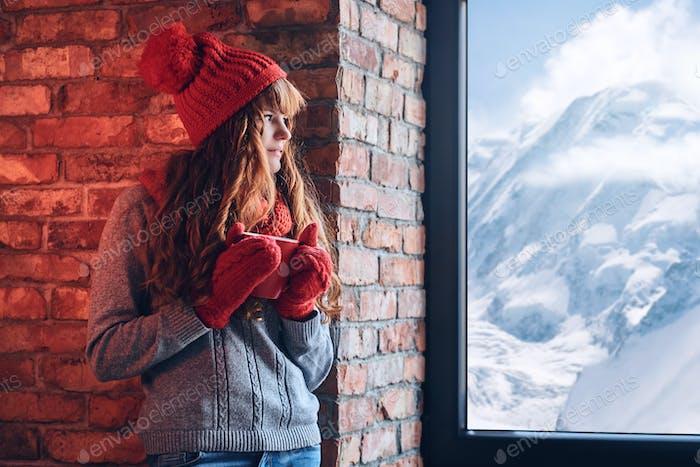 Eine Frau hält Kaffee und blickt über das Fenster auf einem Winterberg.