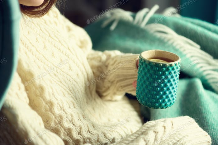 Woman's hand in woolen sweater holding cup of tea with lemon on a cold day. Copy space. Winter