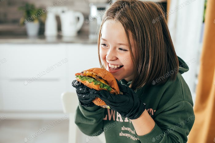 Cute little smilling caucasian girl eating a hamburger at home. Fastfood concept