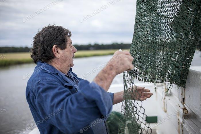 Deckhand mending nets