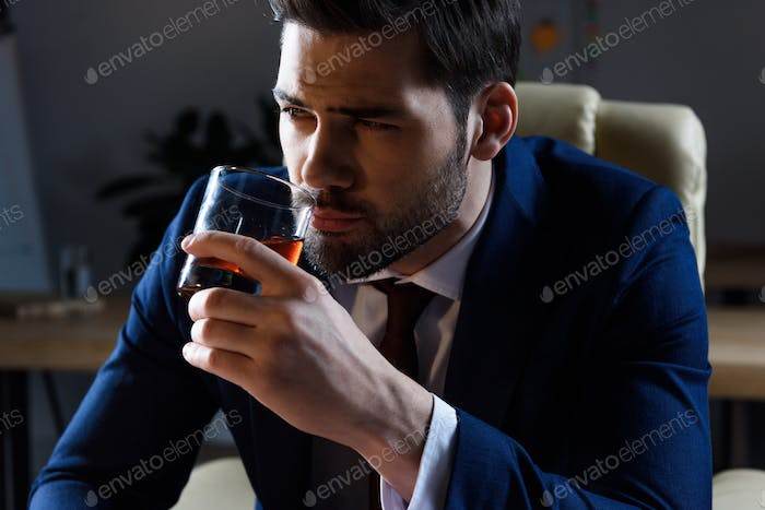 portrait of businessman drinking whiskey and looking away