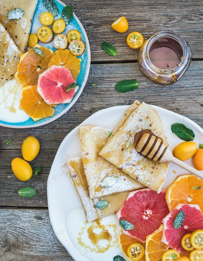 Spring vitamin breakfast set. Thin crepes or pancakes with fresh grapefruit, orange, honey