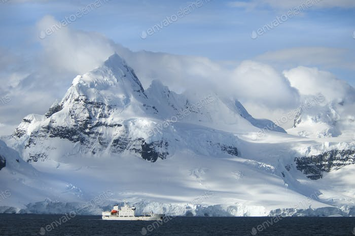 A ship under the towering shape of a mountain range.