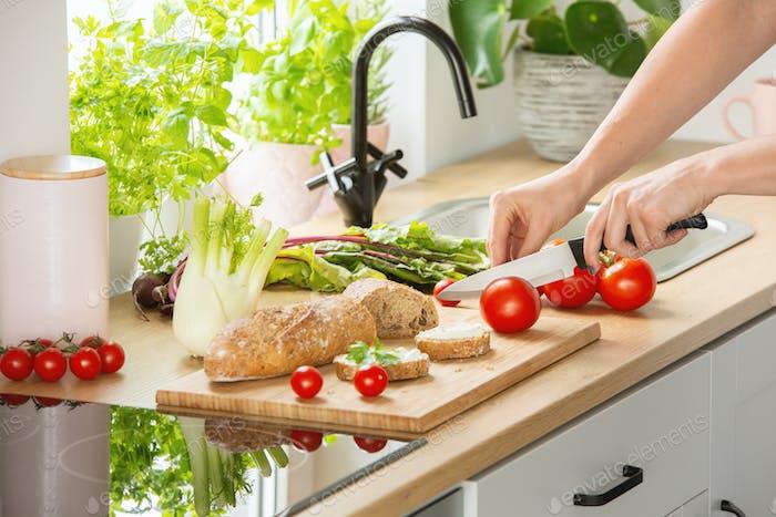 Frau Vorbereitung gesundes Frühstück, Schneiden einer Tomate in zwei Hälften und