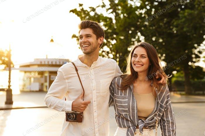 Happy beautiful couple walking in a city street