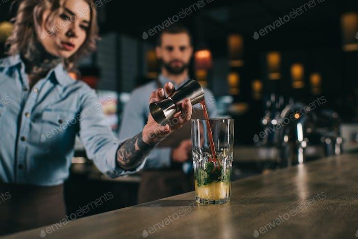 бармен, добавляющий ингредиент в алкогольный напиток в баре