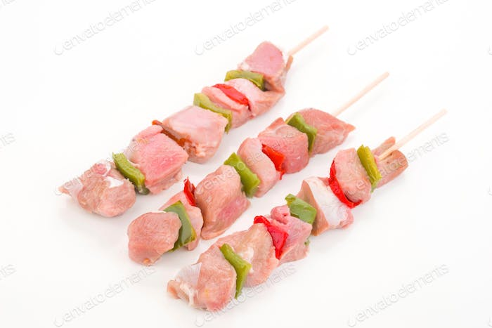 skewers of raw meat and vegetables