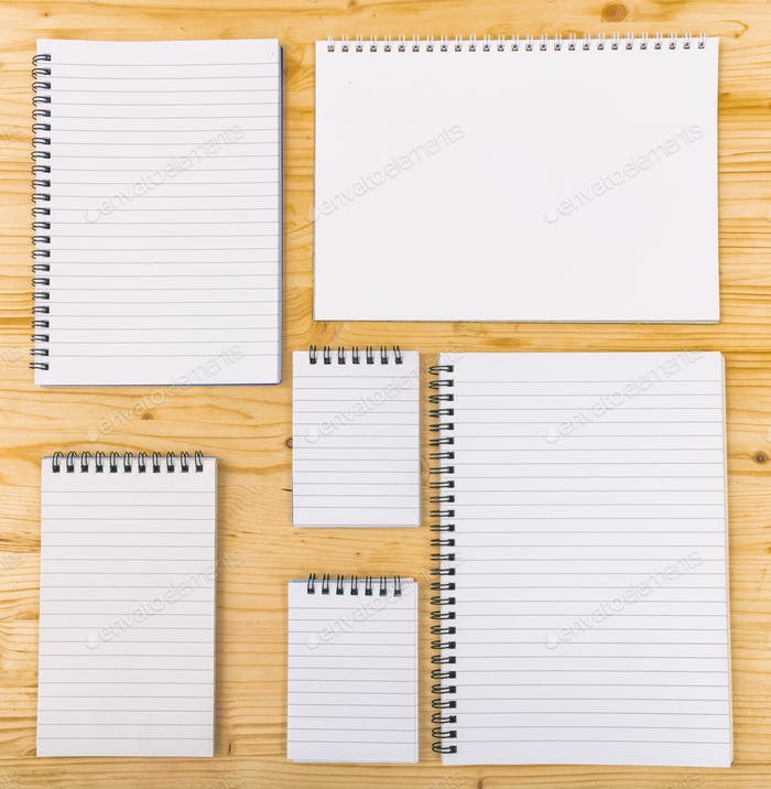 Variety of spiral empty notebooks on wooden background. Copyspace.