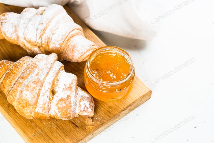 Croissant with jam on white