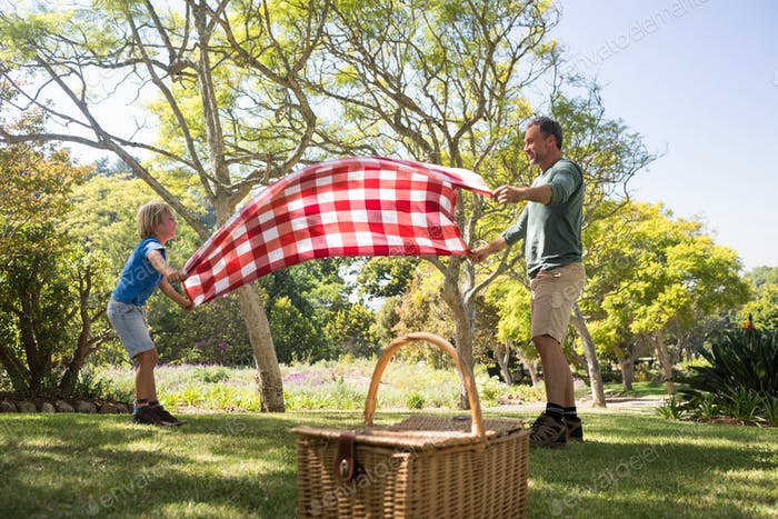 Father and son spreading the picnic blanket