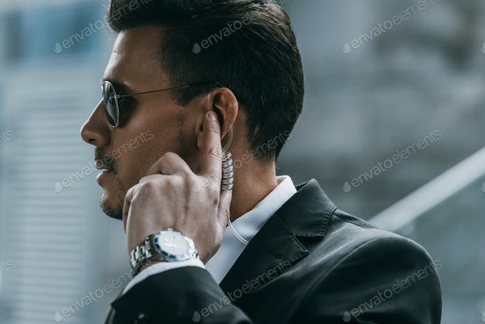 handsome security guard standing and listening message with security earpiece