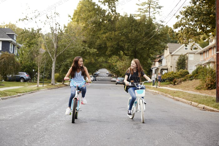 Two teen girls riding bikes in a quiet street, front view