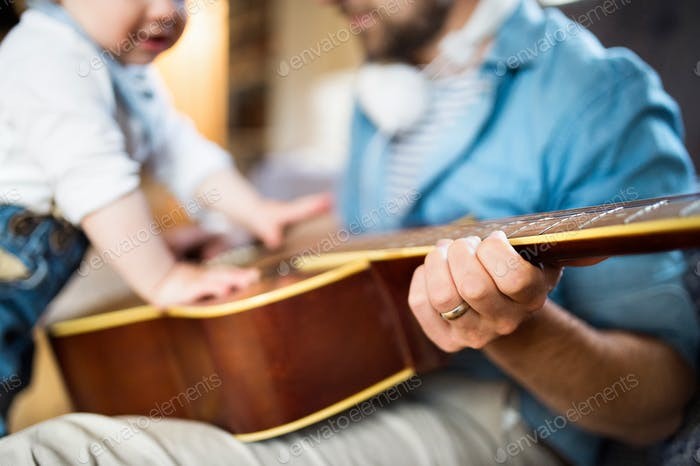 Little boy at home playing guitar with his father.
