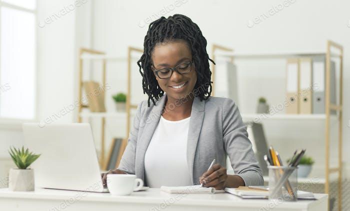 Black Office Girl Sitting At Laptop Taking Notes At Work