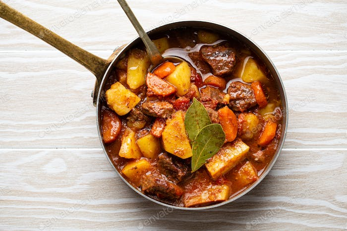 Delicious stew with meat, potatoes, carrot and gravy in old rustic copper pot