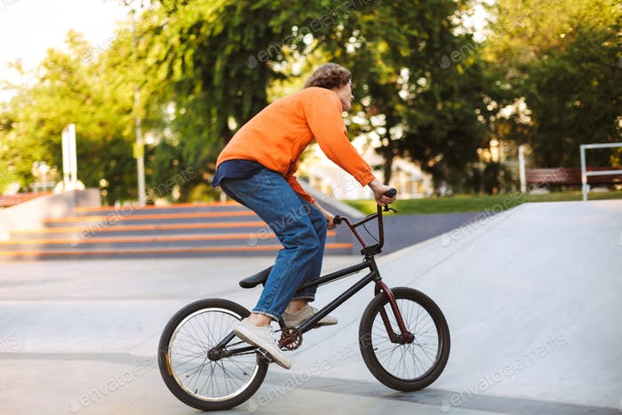 Young guy in orange pullover and jeans from back riding bicycle