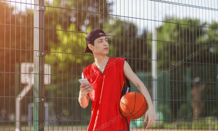 Serious Asian player with smartphone at outdoor basketball arena