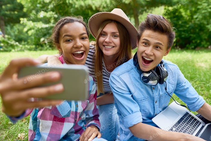 Smiling Teenagers Taking Selfie in Park