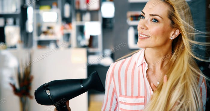 Portrait of beautiful young woman drying hairstyle