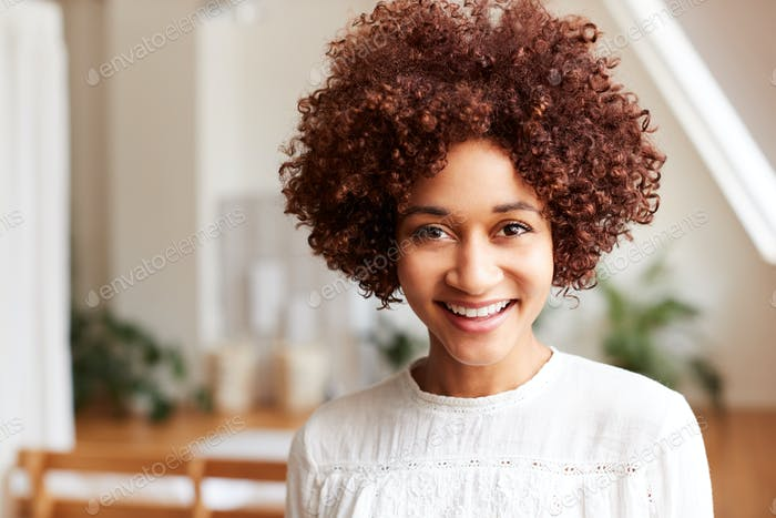 Portrait Of Smiling Young Woman In Loft Apartment