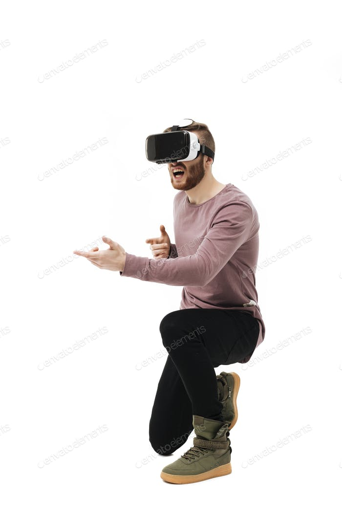 Portrait of cool boy in virtual reality glasses playing in shooter game over white background