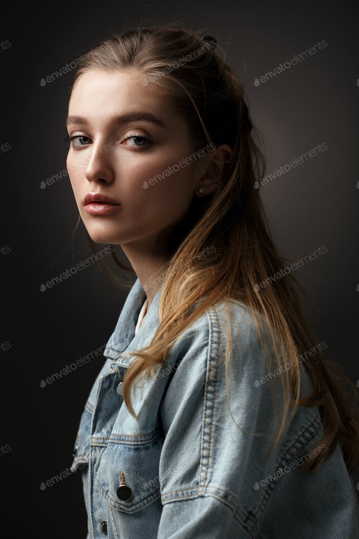 Portrait of beautiful brunette girl with hair tied back dressed in jeans jacket on the dark