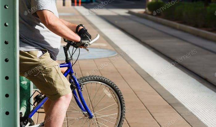 Man Waiting for Train on Platform with Bike