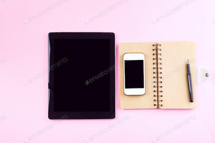 Cuadernos, tableta, lápiz y teléfono Inteligente sobre un Fondo rosa pastel. Concepto de maqueta para Negocios