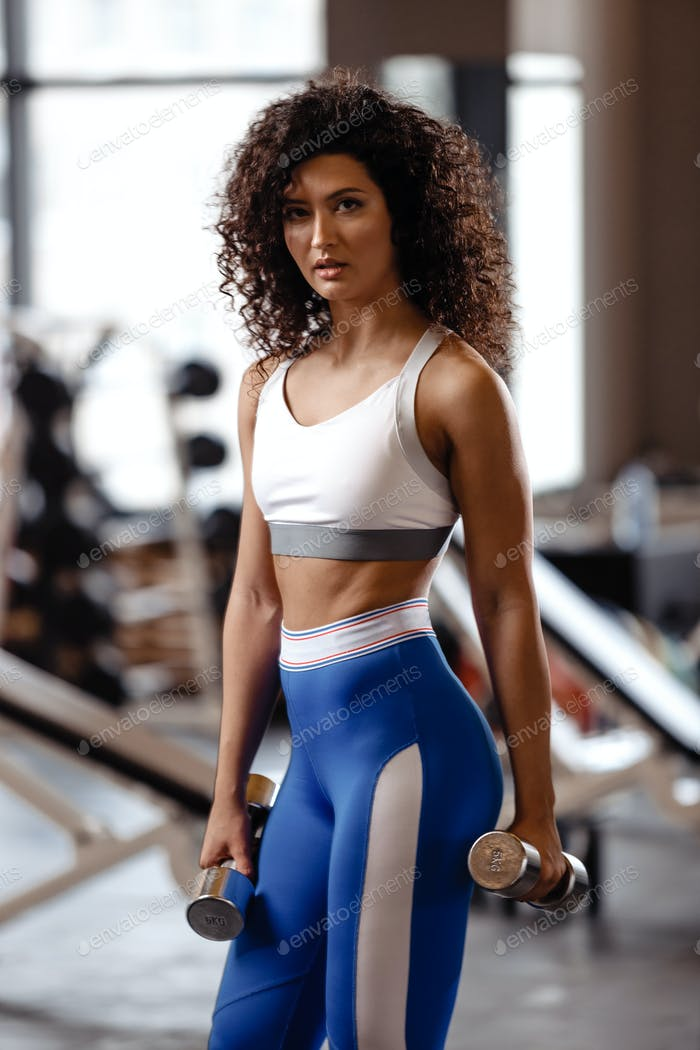 Slim girl with dark curly hair dressed in a sportswear is doing exercises with dumbbells in the