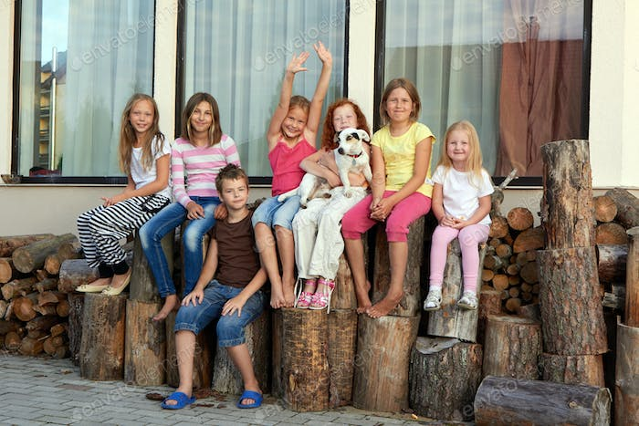 Group of happy little friends sitting on a firewood in a backyard.