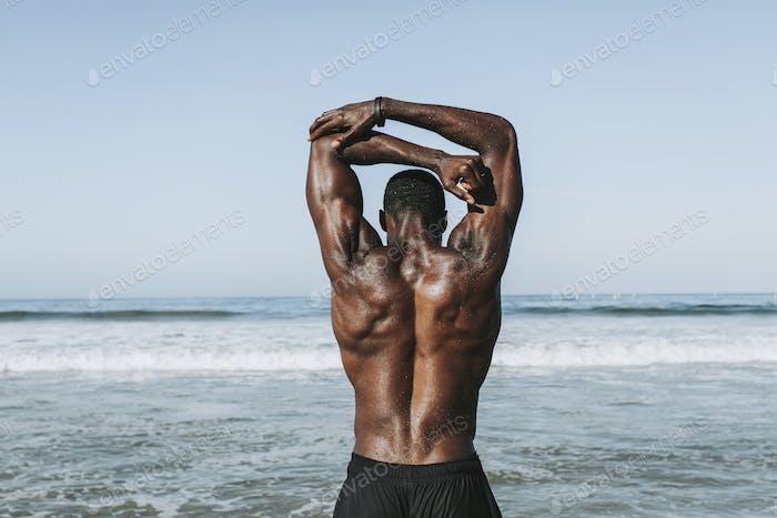 Fit Mann Stretching am Strand