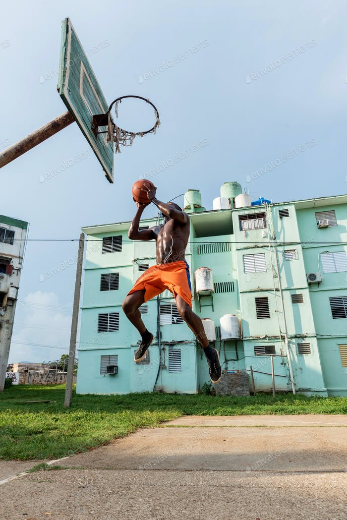 Young African American Man Playing Basketball On Outdoor Court in Cuba