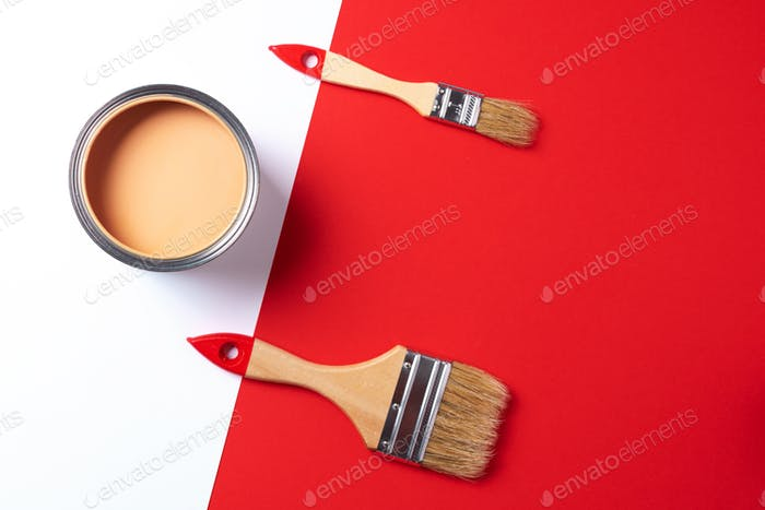 Wooden paint brushes, open paint can on trendy red and white background. Top view, copy space