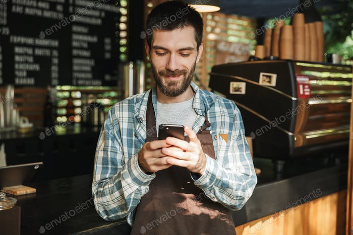 Portrait of caucasian barista guy typing on mobile phone in stre