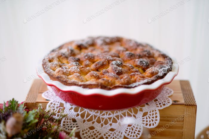 Table with sweet pie in red porcelain tray laid on wooden box